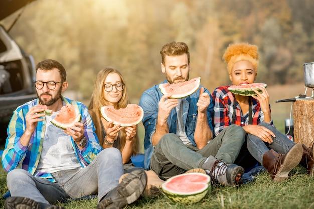 야외 레크리에이션 동안 수박을 먹고 피크닉을 즐기는 다민족 친구들