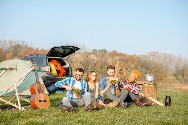 피크닉을 하고 수박을 먹고 호수 근처에 텐트, 자동차, 하이킹 장비를 갖춘 캠핑장에 나란히 앉아 있는 다민족 친구들