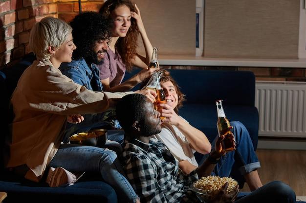 작은 집 파티, 모임, 소파에 앉아 맥주 병 부딪 치기, 지출, 함께 시간 즐기기, 밤에 tv 시청하는 친구의 다민족 그룹. 측면보기