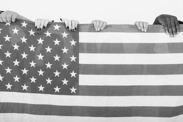 白黒の白い壁に対して団結と多様性を象徴するアメリカの国旗を一緒に持つ友人の多民族グループ