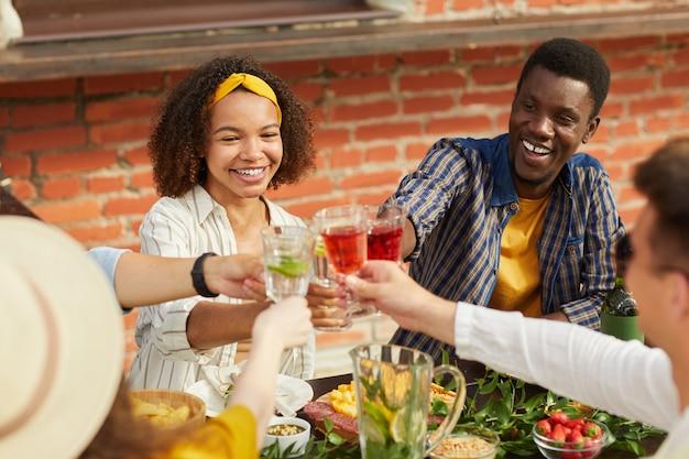 夏に屋外ディナーを楽しみながら乾杯する友人の多民族グループは、元気に笑っている若いアフリカ系アメリカ人の女性に焦点を当てます