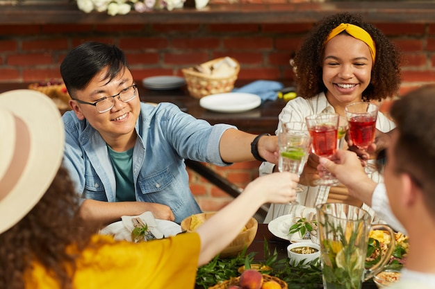 夏に屋外ディナーを楽しみながら乾杯する友人の多民族グループは、元気に笑っている若いアジア人男性に焦点を当てます