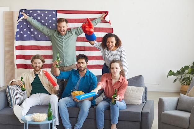 Многонациональная группа друзей смотрит спортивный матч и эмоционально аплодирует, держа в руках американский флаг