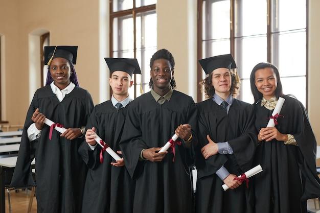 졸업 가운을 입고 학교 강당에 서 있는 동안 카메라를 바라보는 행복한 젊은 사람들의 다민족 그룹