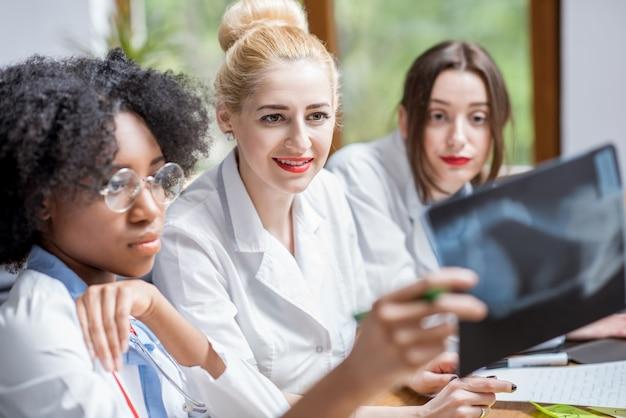 Многонациональная группа студентов-медиков в униформе смотрит на рентгеновский снимок, сидя за столом в современном классе