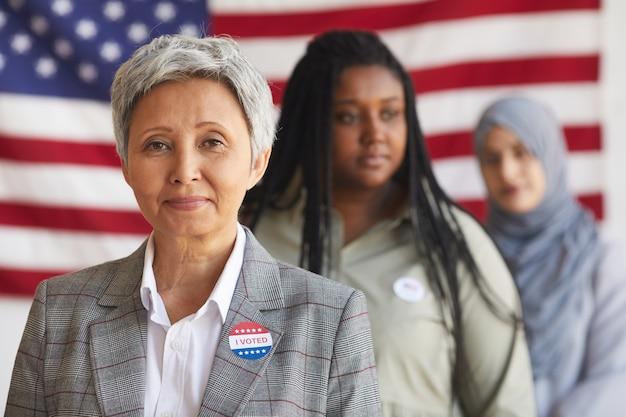 選挙日の投票所での多民族の人々のグループ、i votedステッカー、コピースペースで年配の女性の笑顔に焦点を当てる
