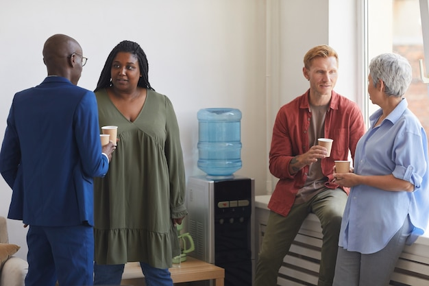 サポートミーティング、コピースペースでウォータークーラーのそばに立っている間にコーヒーを飲み、チャットする人々の多民族グループ