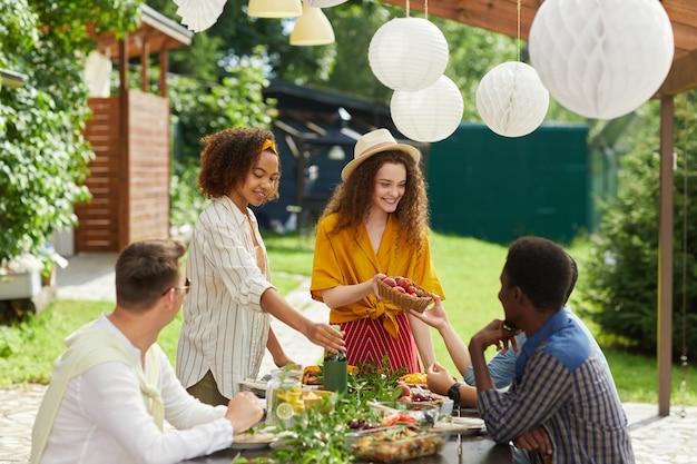 夏に屋外テラスで夕食を楽しんでいる人々の多民族グループは、テーブルを横切って新鮮な果物やベリーを手渡す笑顔の若い女性に焦点を当てる