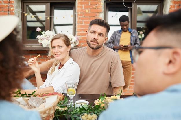 屋外で夕食を楽しんでいる人々の多民族グループ、友人と話すカップルに焦点を当てる