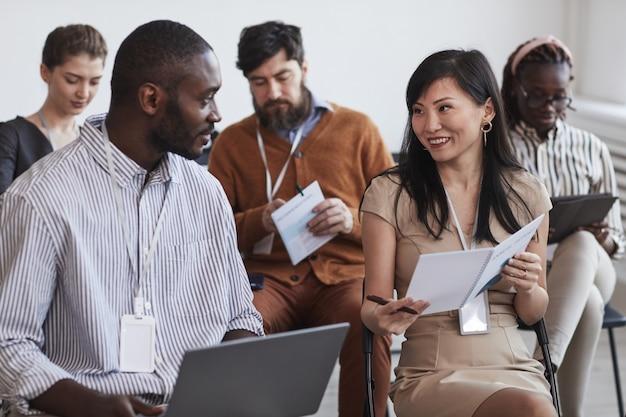 Многонациональная группа людей в аудитории на бизнес-конференции фокусируется на улыбающихся мужчине и женщине, разговаривающих, сидя на стульях в ряду