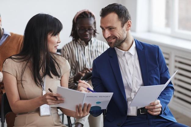 Многонациональная группа людей в аудитории на бизнес-конференции фокусируется на улыбающихся мужчине и женщине, разговаривающих, сидя на стульях