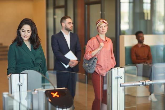 Многонациональная группа людей, проходящих через автоматические ворота при входе в офисное здание, фокусируется на молодой ближневосточной женщине, считывающей удостоверение личности, копировальной площади