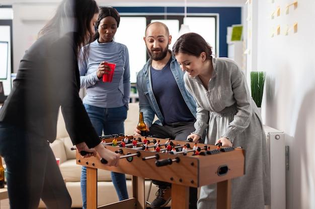 仕事のパーティーやアルコールを楽しんだ後、フーズボールテーブルで遊んでいる人々の多民族グループ