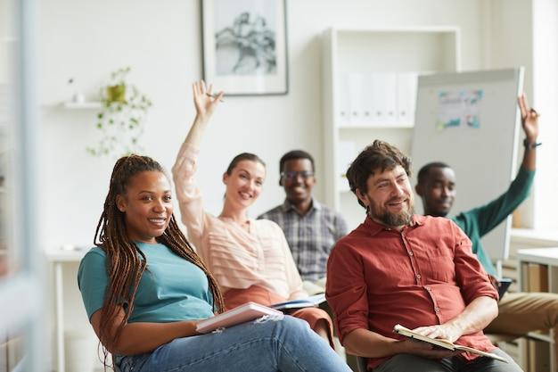 Многонациональная группа людей, поднимающих руки, отвечая на вопросы во время учебного семинара или бизнес-конференции в офисе