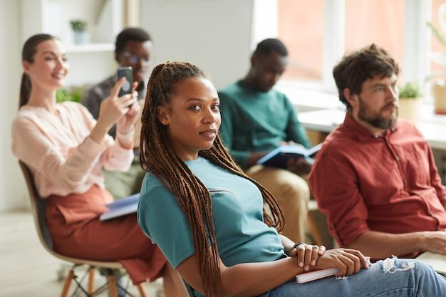 Многонациональная группа людей, сидящих в аудитории во время учебного семинара или бизнес-конференции в офисе