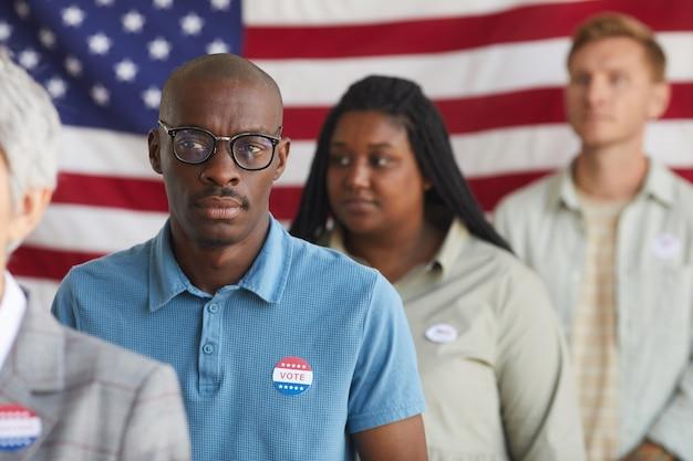 選挙日に投票所に並んでいる多民族の人々のグループ、シャツにi votedステッカー、コピースペースを持ったハゲのアフリカ系アメリカ人男性に焦点を当てる