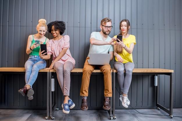 Многонациональная группа молодых людей, одетых в красочные футболки, болтает с гаджетами, сидя в ряд в помещении на фоне стены