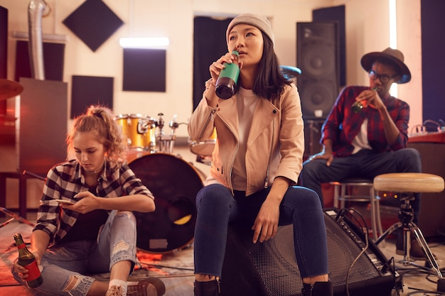 Многоэтническая группа молодых людей в музыкальной студии сосредоточена на азиатской молодой женщине