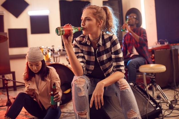 音楽スタジオの若者の多民族グループはかなり若い女性に焦点を当てています