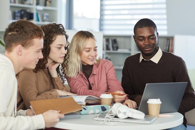 Многонациональная группа молодых людей, обучающихся вместе, сидя за столом в библиотеке колледжа и глядя на экран ноутбука