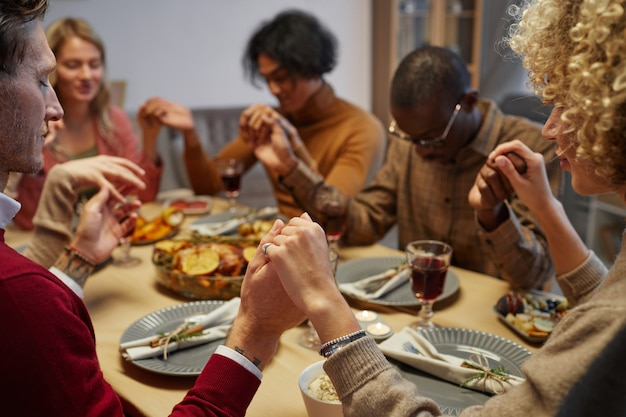 Multi-ethnic group of people holding hands while praying at thanksgiving dinner with friends and family, focus on foreground,