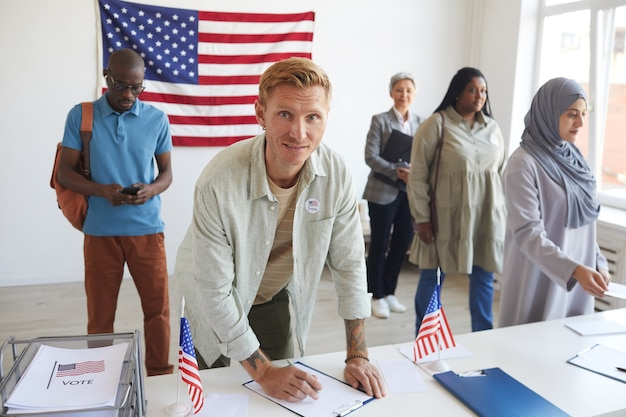 Multi-ethnic group of people registering at polling station decorated with american flags on election day, focus on young man signing ballot forms and , copy space
