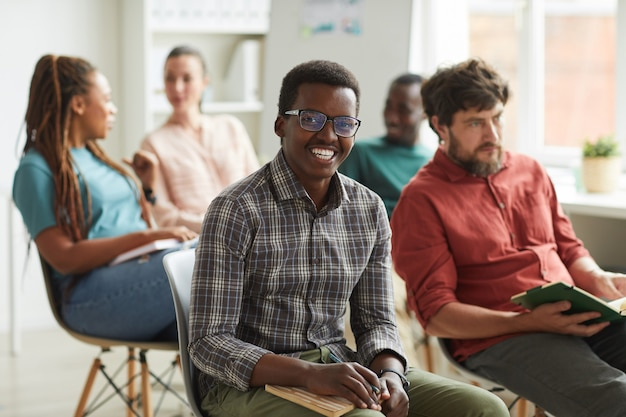 Multi-ethnic group of people sitting in audience during training seminar or business conference in office
