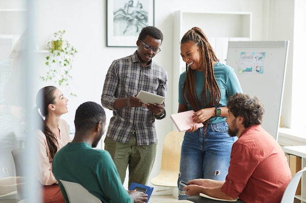 Multi-ethnic group of people sitting in circle while discussing business project in office, focus on smiling african-american woman talking to colleague standing up