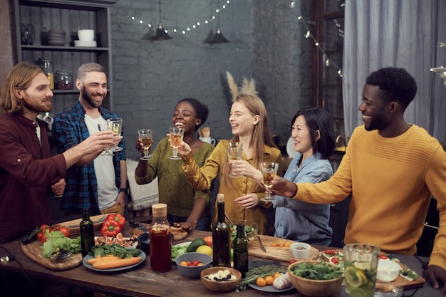 Multi-ethnic group of people toasting at dinner party