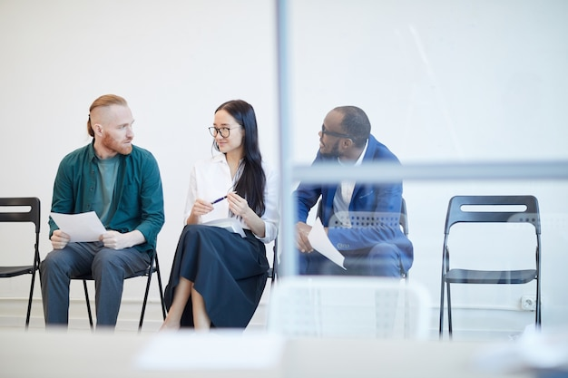 Multi-ethnic group of people waiting in line for job interview and chatting behind glass wall , copy space