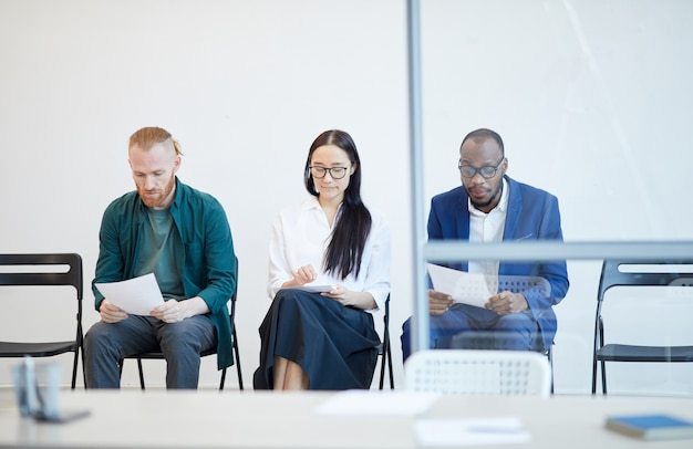 Multi-ethnic group of people waiting in line for job interview and holding cv behind glass wall , copy space