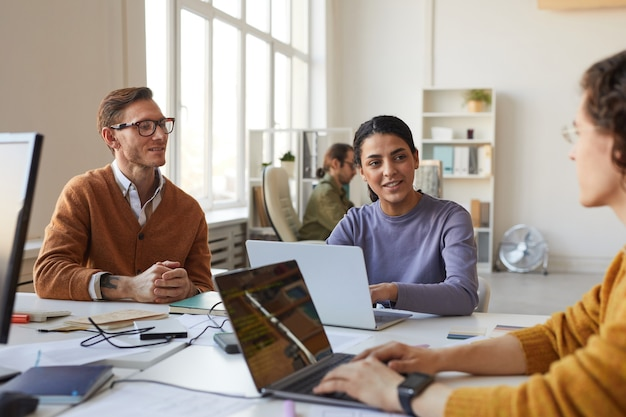 Multi-ethnic group of young business people discussing startup project while working at desk in white office interior, copy space