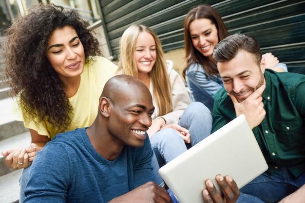 Gruppo multietnico di giovani che esaminano un computer tablet