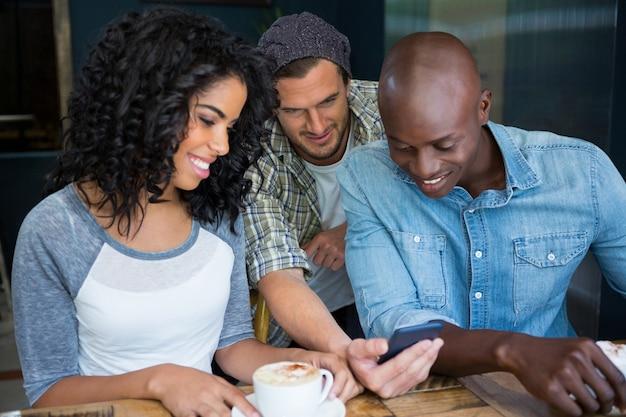 Многоэтнические друзья мужского и женского пола, использующие мобильный телефон в кафе