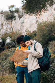 Multi ethnic male hiker finding the destination on map in the forest