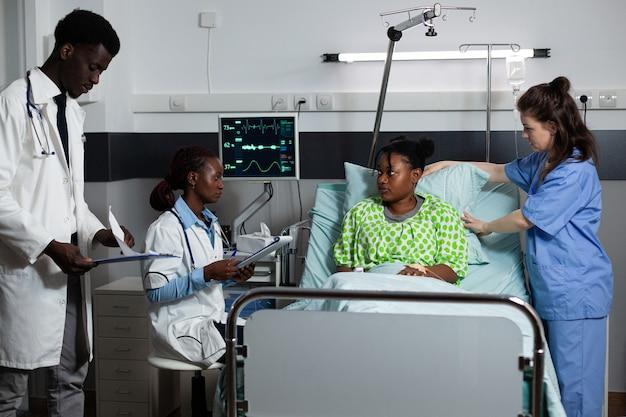 診療所の病棟のベッドで若い人に相談する多民族医療チーム。病気、病気についてアフリカの民族の患者に話している白人の看護師とアフリカ系アメリカ人の医師