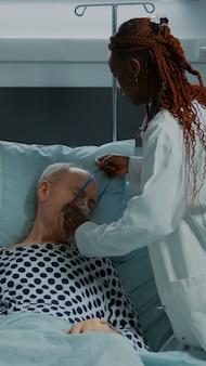 病気の患者を助ける多民族の看護師と医師