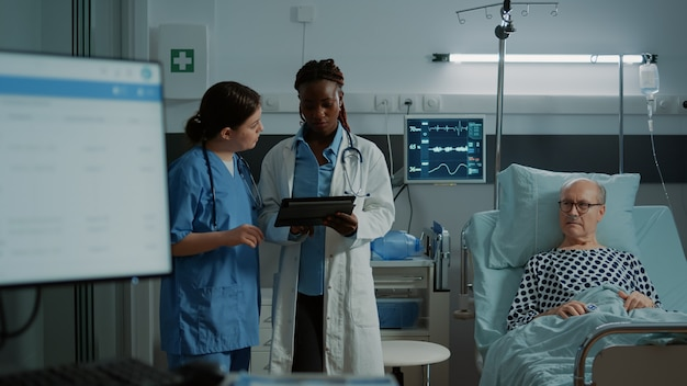 テストのためにタブレットを見ている多民族の看護師と医師