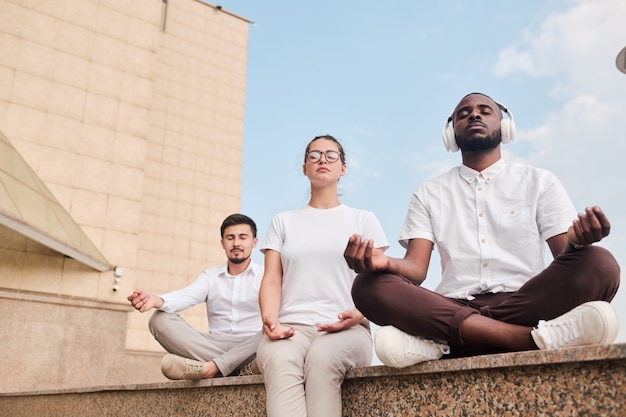 Multi-ethnic people meditating in city