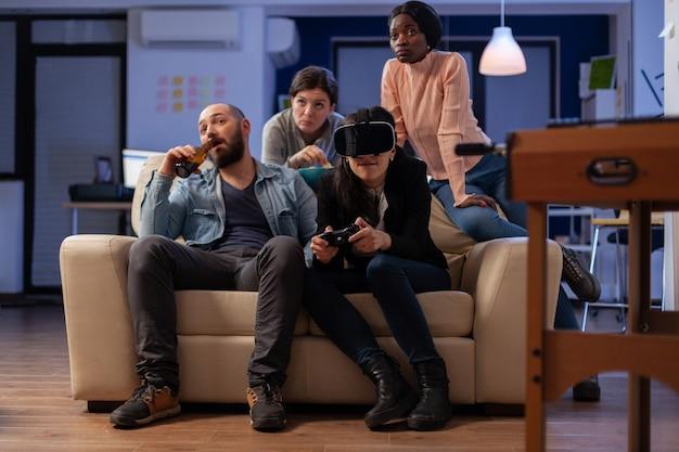 仲間の多民族チームは、オフィスパーティーで働いた後、vrメガネで遊んでいます。さまざまな友達のグループが、勝利のお祝いのためにコンソールコントローラーのジョイスティックでゲーム体験を楽しんでいます