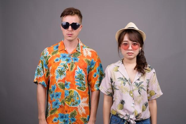 サングラスとアロハシャツを着た多民族の観光客のカップル