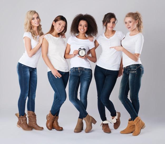 Donne multietniche che tengono un orologio