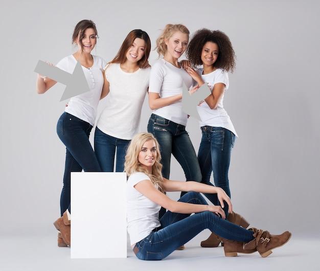 Donne multietniche che mostrano sulla lavagna bianca