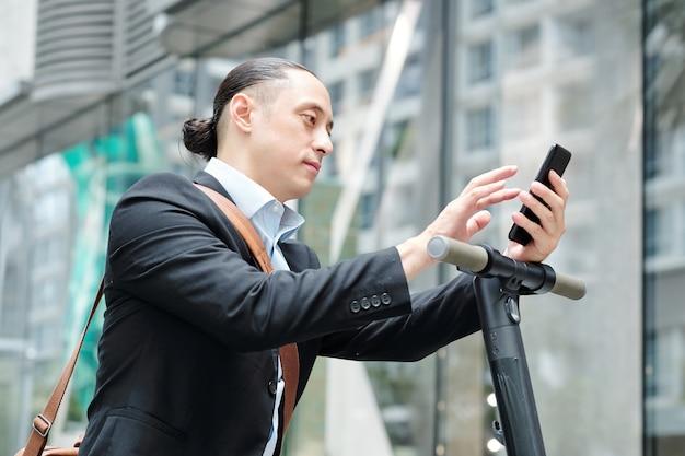 電動スクーターの上に立ってスマートフォンで通知をチェックする多民族の青年実業家