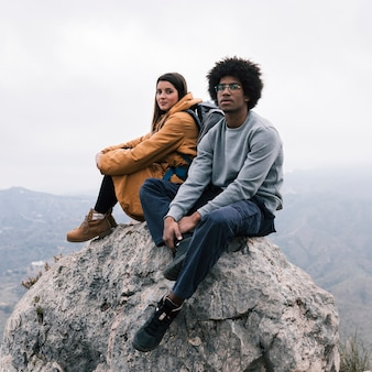 Multi ethnic young couple sitting on top of rock looking at camera