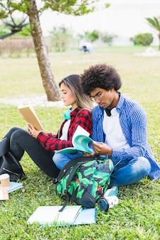 本を一緒に読んでキャンパス内に座っている多民族の若いカップル学生