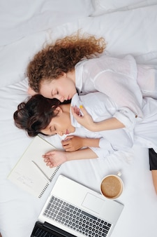 Multi-ethnic young lesbian couple fell asleep when doing homework in bed