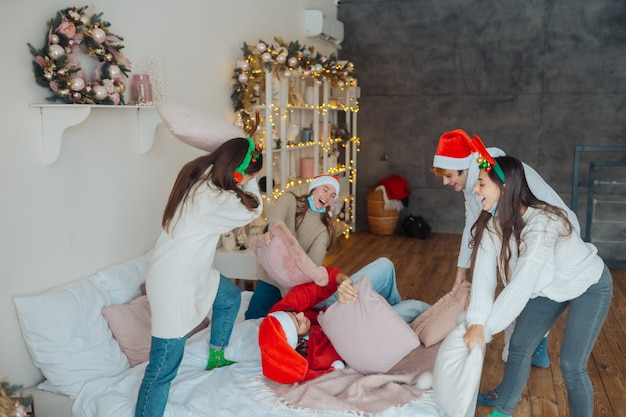 I giovani multietnici si divertono a litigare sui cuscini alla vigilia di capodanno