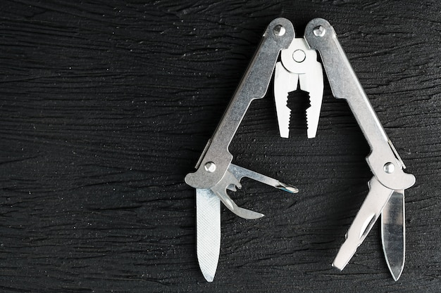 Multi-functional tool on a black textural background.