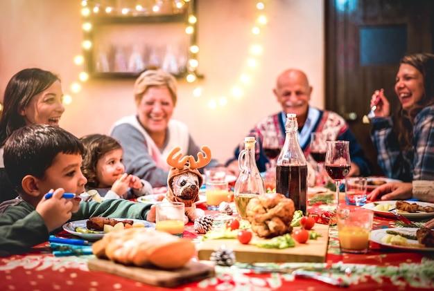 クリスマスの夕食会で楽しんでいる多世代の大家族-トナカイ人形に選択的な焦点